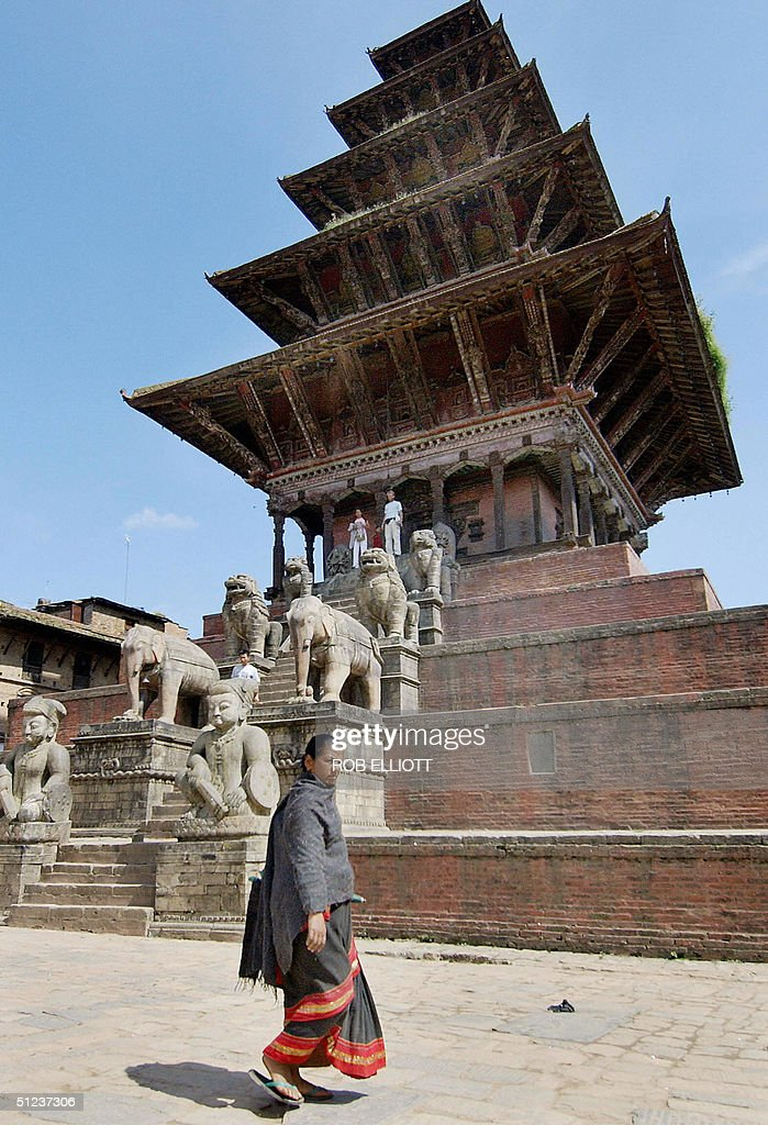 In this picture taken 25 August 2004 a Nepalese woman walks past the towering fivestorey pagoda style temple of goddess Siddhi Laxmi and god...