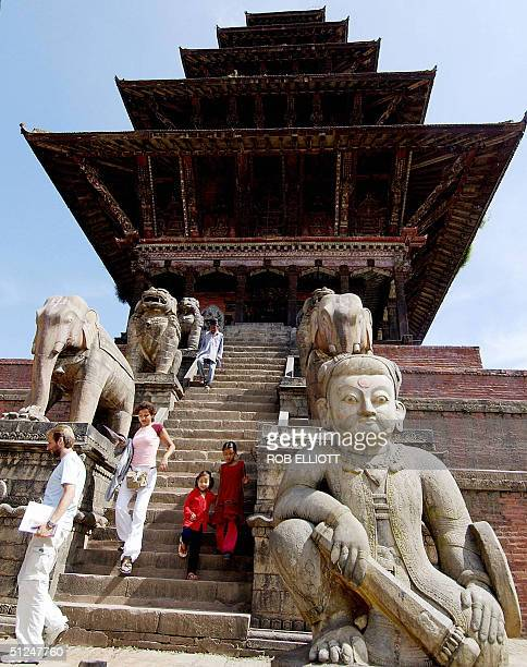 In this picture taken 25 August 2004 foreign tourists descend the steps of the towering five storey pagoda style temple of Hindu Goddess Siddhi Laxmi...