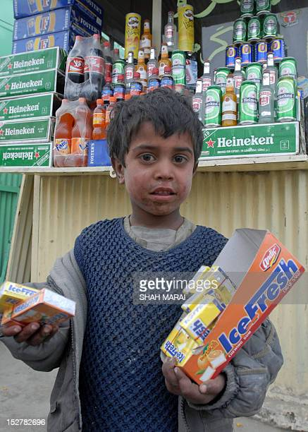 In this picture taken 25 February 2007 an Afghan boy poses with packs of chewing gum at a shop in Bush Bazaar in Kabul Packs of readymade omlettes...