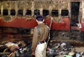 In this picture taken early 28 February 2002 an Indian policeman looks towards a burnt train coach and belongings of Hindu activists at Godhra...