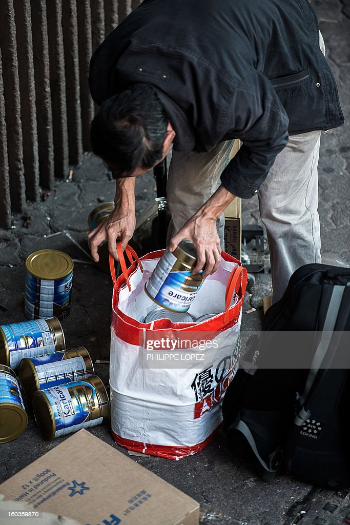 In this picture taken in Hong Kong on January 29, 2013, a mainland Chinese packs a bag with baby formula as he queues up to get his packages weighted at the Sheung Shui train station prior to his journey back to mainland China. Hong Kong is mulling to make baby formula a 'reserved commodity' to ensure sufficient supply, an official said on January 30, 2013, after mainland Chinese who flocked to buy the item sparked shortage fears. AFP PHOTO / Philippe Lopez
