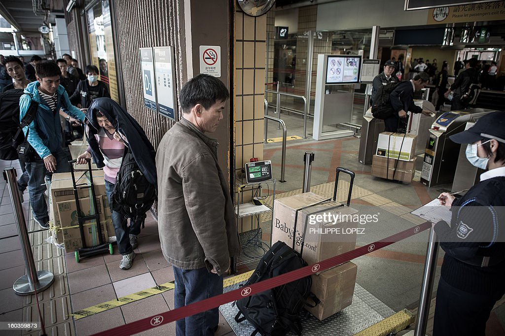 In this picture taken in Hong Kong on January 29, 2013, a mainland Chinese gets his packages weighted at the Sheung Shui train station prior to his journey back to mainland China. Hong Kong is mulling to make baby formula a 'reserved commodity' to ensure sufficient supply, an official said on January 30, 2013, after mainland Chinese who flocked to buy the item sparked shortage fears. AFP PHOTO / Philippe Lopez