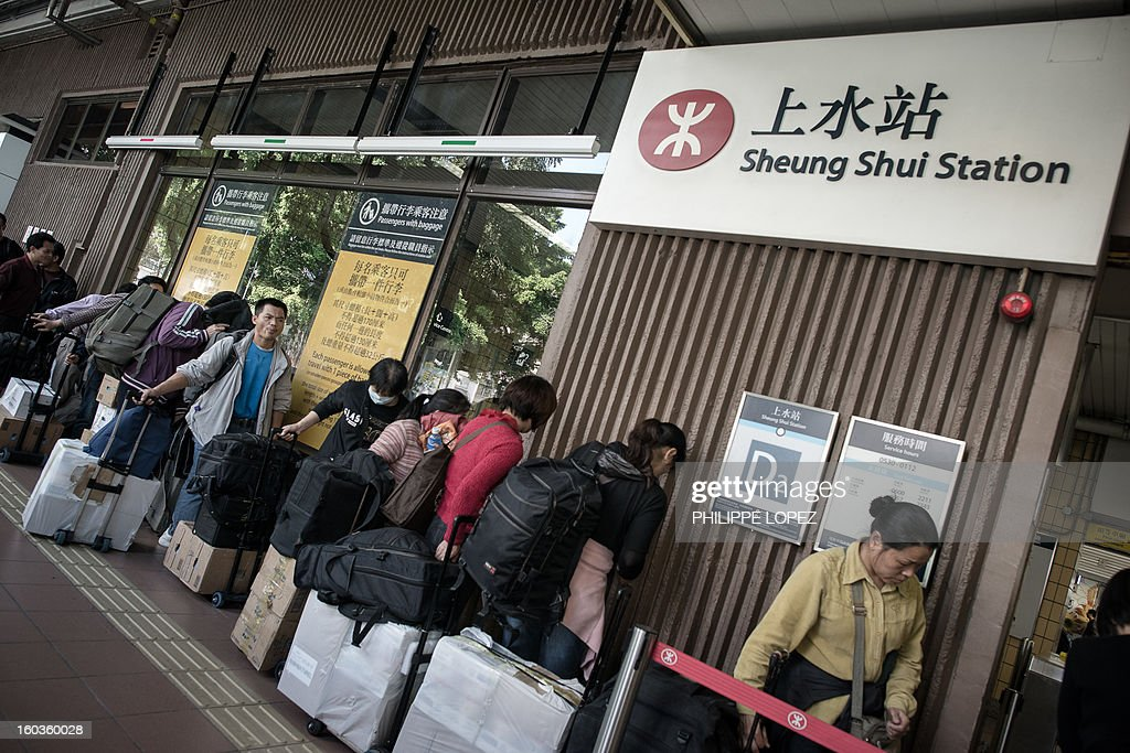 In this picture taken in Hong Kong on January 29, 2013, people queue up to get their packages weighed at the Sheung Shui train station prior to their journey to mainland China. Hong Kong is mulling to make baby formula a 'reserved commodity' to ensure sufficient supply, an official said on January 30, 2013, after mainland Chinese who flocked to buy the item sparked shortage fears. AFP PHOTO / Philippe Lopez