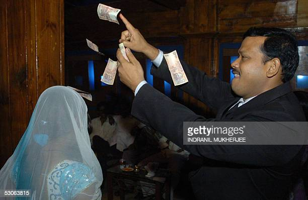 In this picture taken late 06 May 2005 An Indian dancer is showered with currency notes by a steward on behalf of a customer as she performs a...