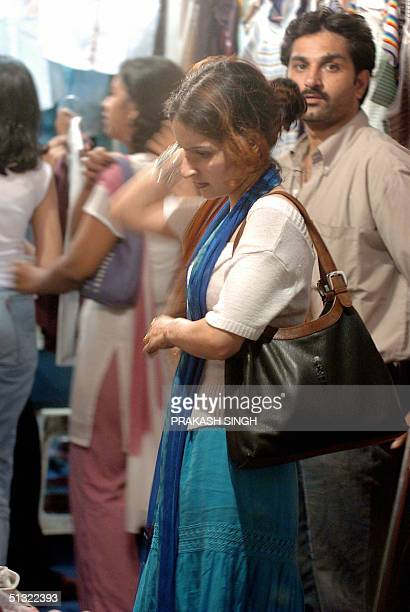 In this picture taken late 16 September 2004 an Indian woman dressed in a westernstyle outfit does some shopping at a night market in New Delhi The...