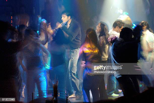 In this picture taken late 17 September 2004 young Indians dance at a nightclub at a luxury hotel in New Delhi The blighted poor still roam the...