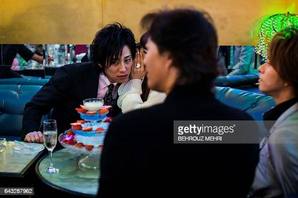 In this picture taken late on January 27 a female customer whispers to her Japanese host Ichi at a host club in the Kabukicho redlight district in...