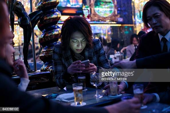 In this picture taken late on January 27 a male host checks his phone as he sits with other hosts and a female customer at a host club in the...