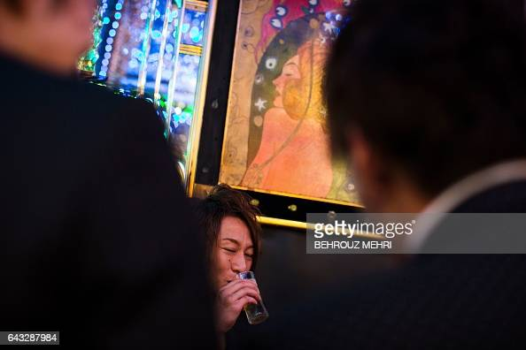 In this picture taken late on January 27 a male host drinks as he sits with other hosts and a female customer at a host club in the Kabukicho...