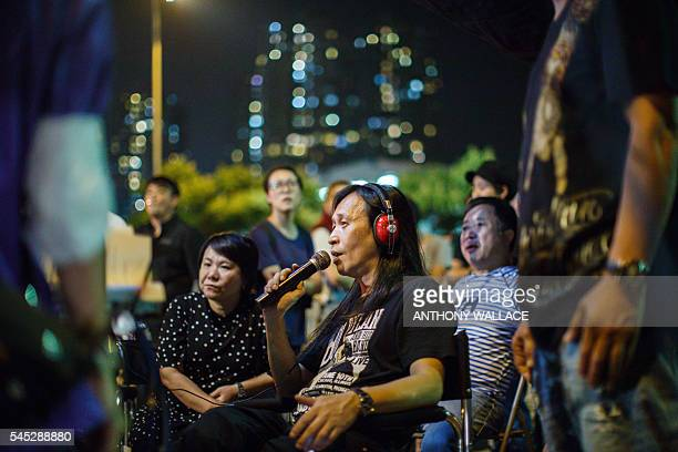 In this picture taken late on May 23 members of a film crew working with local director Herman Yau listen as he speaks over the microphone to his...