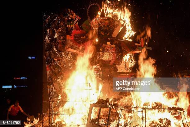 In this picture taken late September 12 an ethnic MalaysianChinese devotee sets fire to a paperstatue of Chinese deity 'Da Shi Ye' or Guardian God of...