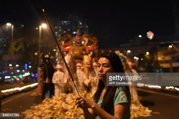 In this picture taken late September 12 an ethnic MalaysianChinese devotee offers prayers in front of a paper statue of Chinese deity 'Da Shi Ye' or...