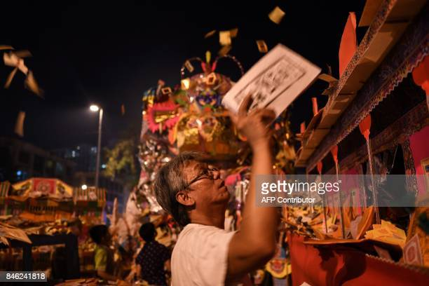 In this picture taken late September 12 an ethnic MalaysianChinese devotee throws mock currency to be burned by a paper statue of Chinese deity 'Da...