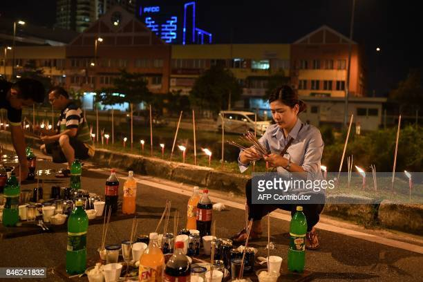 In this picture taken late September 12 an ethnic MalaysianChinese devotee prepares food offerings to mark the Hungry Ghost Festival in Kuala Lumpur...