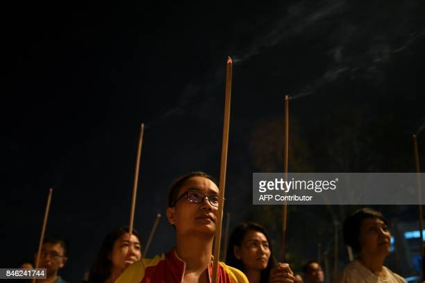 In this picture taken late September 12 ethnic MalaysianChinese devotees burn joss sticks in front of a paper statue of Chinese deity 'Da Shi Ye' or...