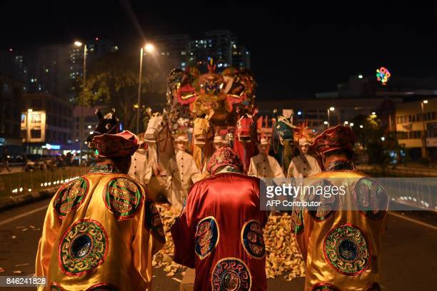TOPSHOT In this picture taken late September 12 Taoist monks offer prayers in front of a paperstatue of Chinese deity 'Da Shi Ye' or Guardian God of...