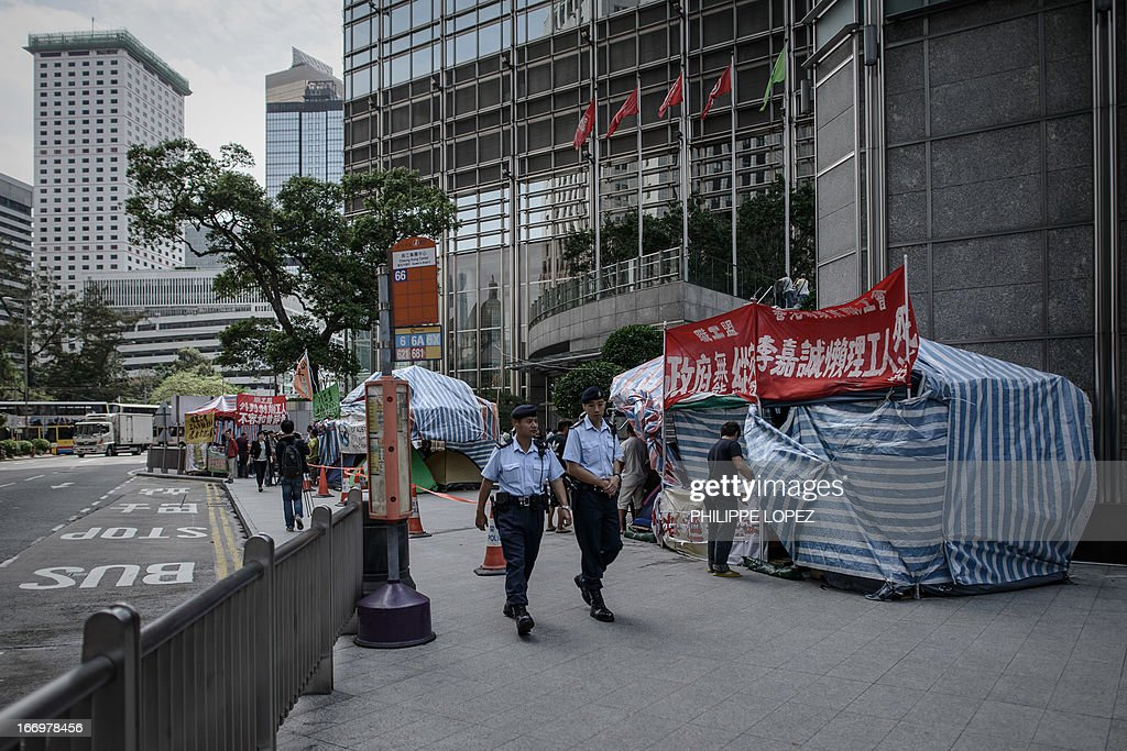 In this picture taken on April 18, 2013, policemen walk past the camp set up by dockers asking for an increase in pay and better working conditions in Hong Kong. Striking Hong Kong dock workers camped outside the headquarters of Asia's richest man Li Ka-shing pledged to stay put on April 19 despite the collapse of a contractor at the centre of the dispute. AFP PHOTO / Philippe Lopez