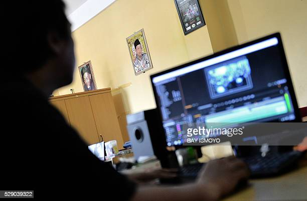 In this picture taken on April 27 2016 an Aswaja TV crew edits a television program on a tv screen at their office in Jakarta as their previous...