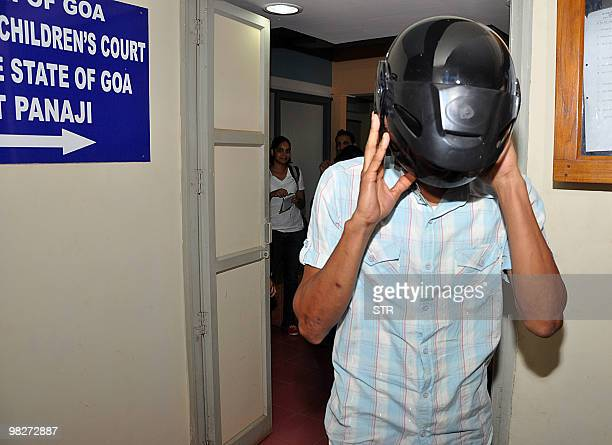 In this picture taken on April 5 prime accused in the Scarlet Keeling case Samson D'Souza covers his head with a motorcycle helmet the Children's...