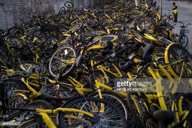 In this picture taken on April 6 a worker stands next to a pile of shared bicycles at a repair centre in Beijing A booming rental bike business has...