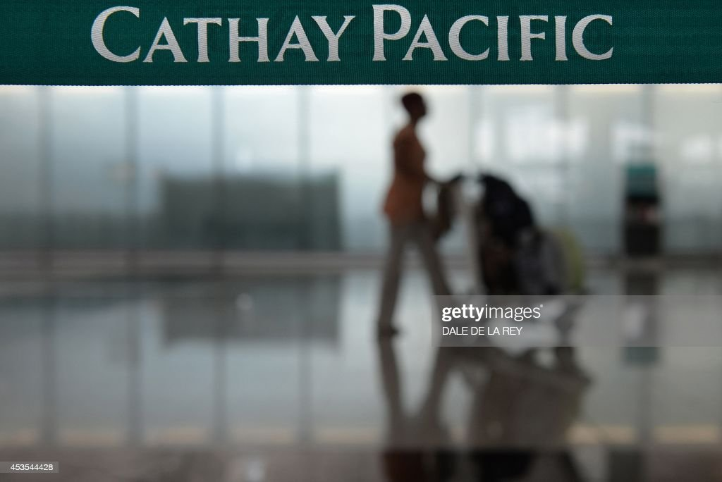 In this picture taken on August 10 a woman walks past checkin counters for Hong Kong flag carrier Cathay Pacific at Hong Kong's international airport...