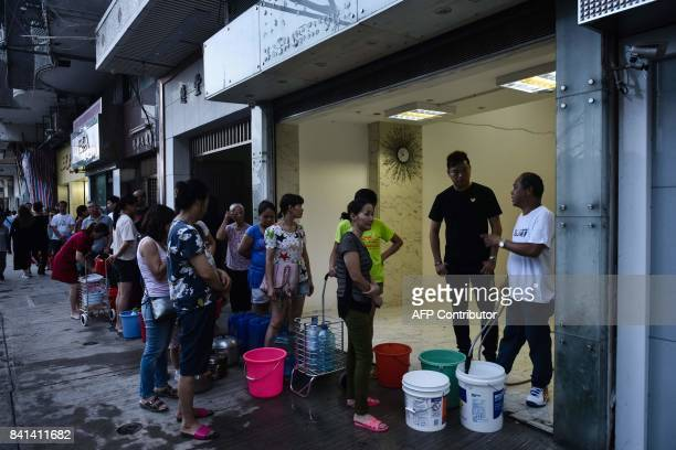 In this picture taken on August 24 residents queue up for water after their supplies were cut off during Typhoon Hato in Macau When Typhoon Hato...
