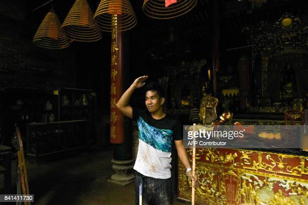 In this picture taken on August 25 a volunteer indicates how high the floodwaters rose in a temple during Typhoon Hato in Macau When Typhoon Hato...