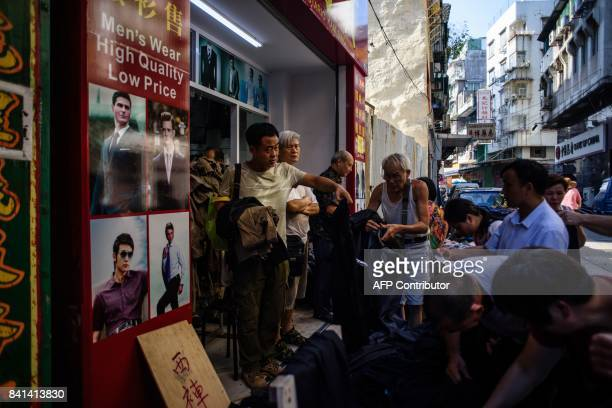 In this picture taken on August 29 residents look through piles of stock damaged during Typhoon Hato being sold at bargain prices in Macau When...