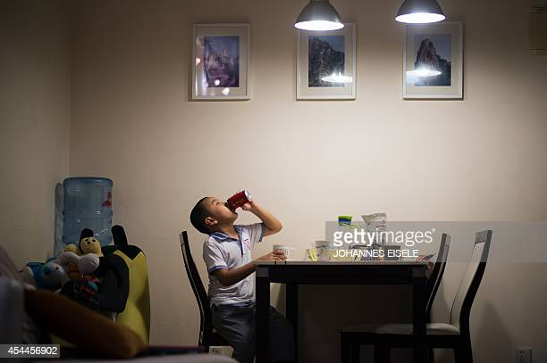 In this picture taken on August 31 seven year old Wei Yueran who also has the English name Harney has a drink before his bedtime in Shanghai After...
