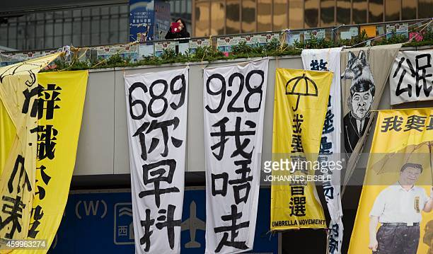 STORY 'HONG KONGCHINAPROTESTSDEMOCRACYLANGUAGE' FEATURE In this picture taken on December 4 a woman stands above banners with the symbols 689 and 928...
