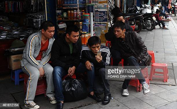 In this picture taken on December 5 men reads news from a smartphone on a commercial street in downtown Hanoi Vietnam's Prime Minister Nguyen Tan...