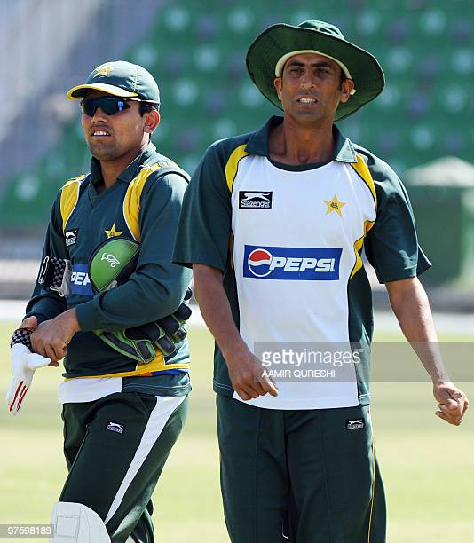 In this picture taken on February 28 Pakistan�s cricket captain Younus Khan arrives with teammate Kamran Akmal for a training session at The Gaddafi...