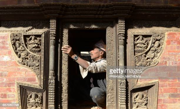In this picture taken on February 8 a worker renovates a heritage site at Durbar Square in Kathmandu Caretaker Deepak Shrestha padlocked shut the...