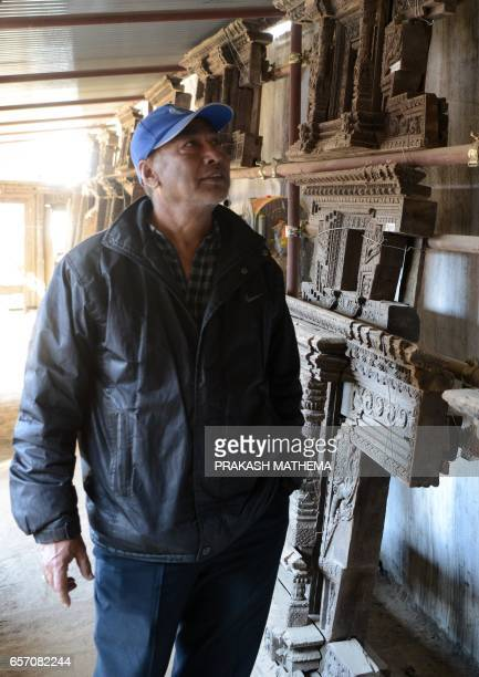 In this picture taken on February 8 Trilokya Mohan Narayan temple caretaker Deepak Shrestha looks at artifacts during a interview with AFP in Durbar...