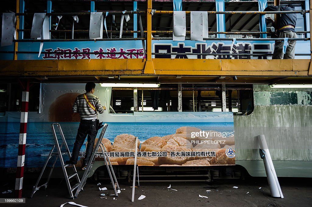 In this picture taken on January 11, 2013 workers wrap an adhesive advert around a tram at the Whitty street depot, the main terminus stop of the Hong Kong Tramway Ltd, in Hong Kong. Trundling along slowly against a backdrop of glittering skyscrapers, Hong Kong's trams are entering a new phase of their life but their well-loved retro look is here to stay. AFP PHOTO / Philippe Lopez