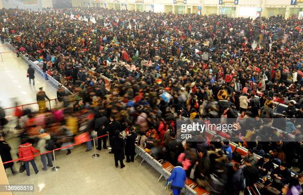 In this picture taken on January 13 Chinese passengers queue up to board trains as they return home for the lunar Chinese New Year holiday at a...