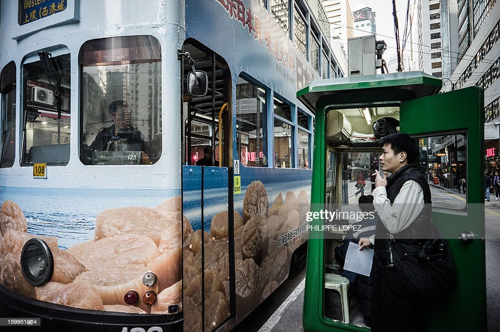 In this picture taken on January 14, 2013 a tram arrives at a terminus stop in Hong Kong. Trundling along slowly against a backdrop of glittering skyscrapers, Hong Kong's trams are entering a new phase of their life but their well-loved retro look is here to stay. AFP PHOTO / Philippe Lopez