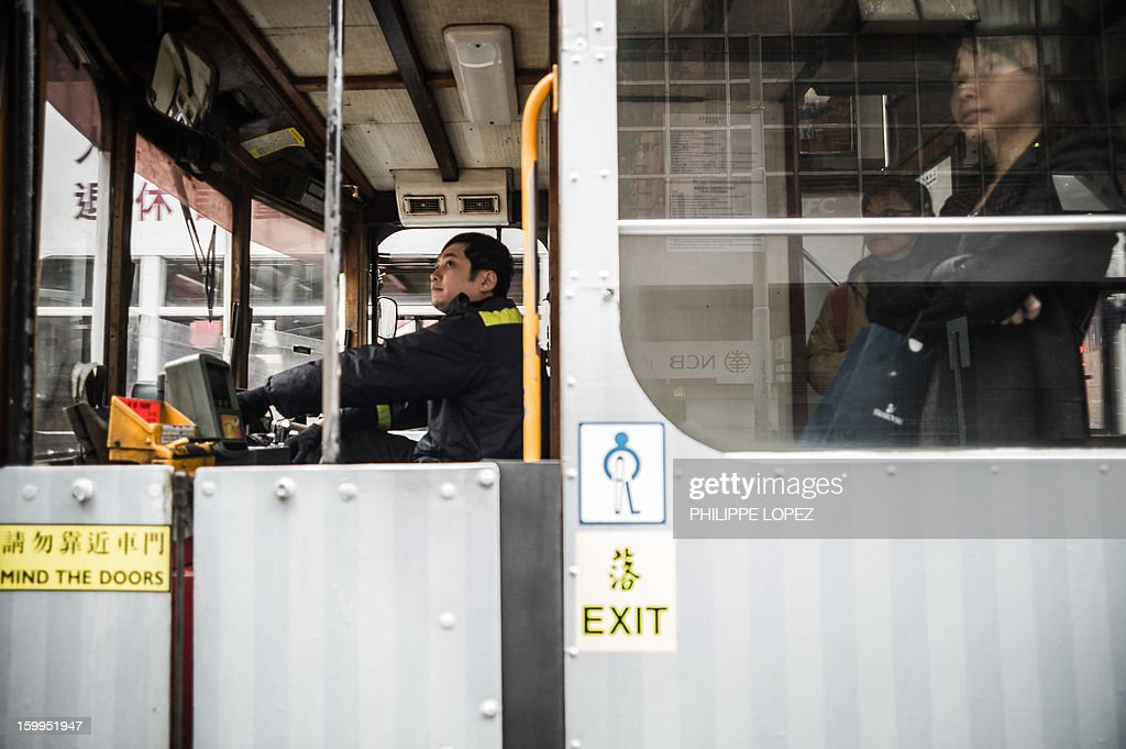 In this picture taken on January 15, 2013 a driver looks into the mirrors of his tram in Hong Kong. Trundling along slowly against a backdrop of glittering skyscrapers, Hong Kong's trams are entering a new phase of their life but their well-loved retro look is here to stay. AFP PHOTO / Philippe Lopez