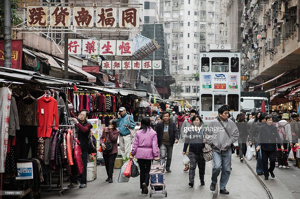 In this picture taken on January 15, 2013 a tram (R) goes through a street market in Hong Kong. Trundling along slowly against a backdrop of glittering skyscrapers, Hong Kong's trams are entering a new phase of their life but their well-loved retro look is here to stay. AFP PHOTO / Philippe Lopez