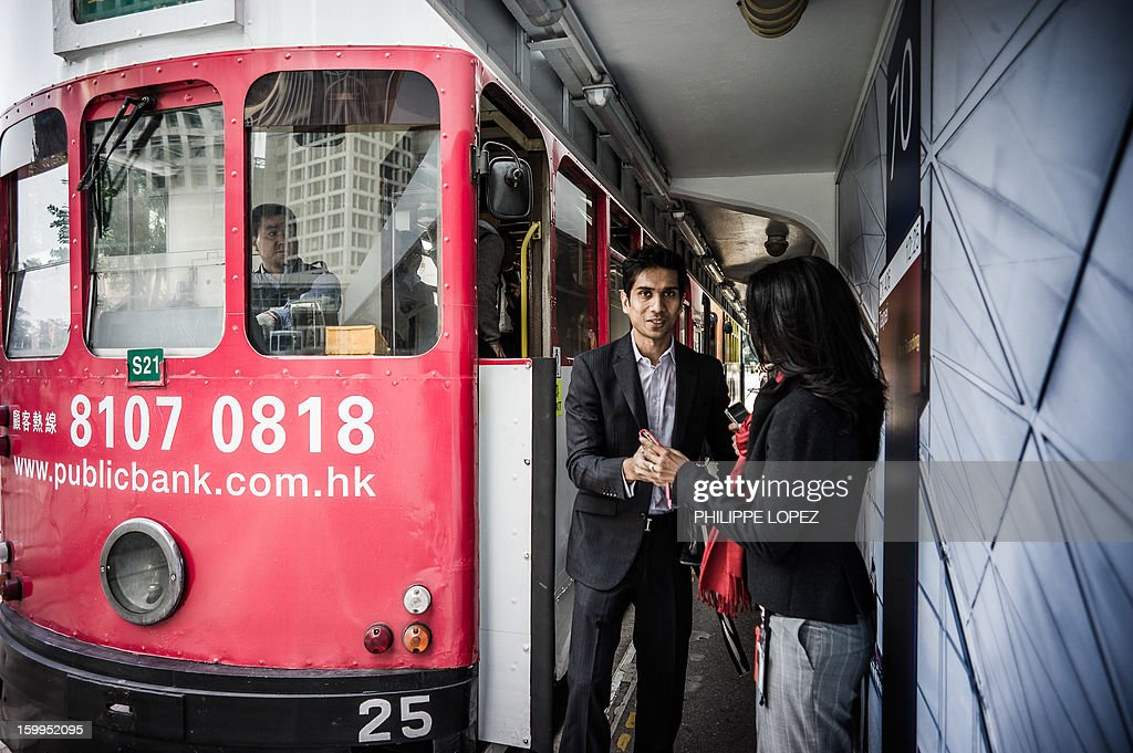 In this picture taken on January 17, 2013 a man and a woman exit a tram in Hong Kong. Trundling along slowly against a backdrop of glittering skyscrapers, Hong Kong's trams are entering a new phase of their life but their well-loved retro look is here to stay. AFP PHOTO / Philippe Lopez