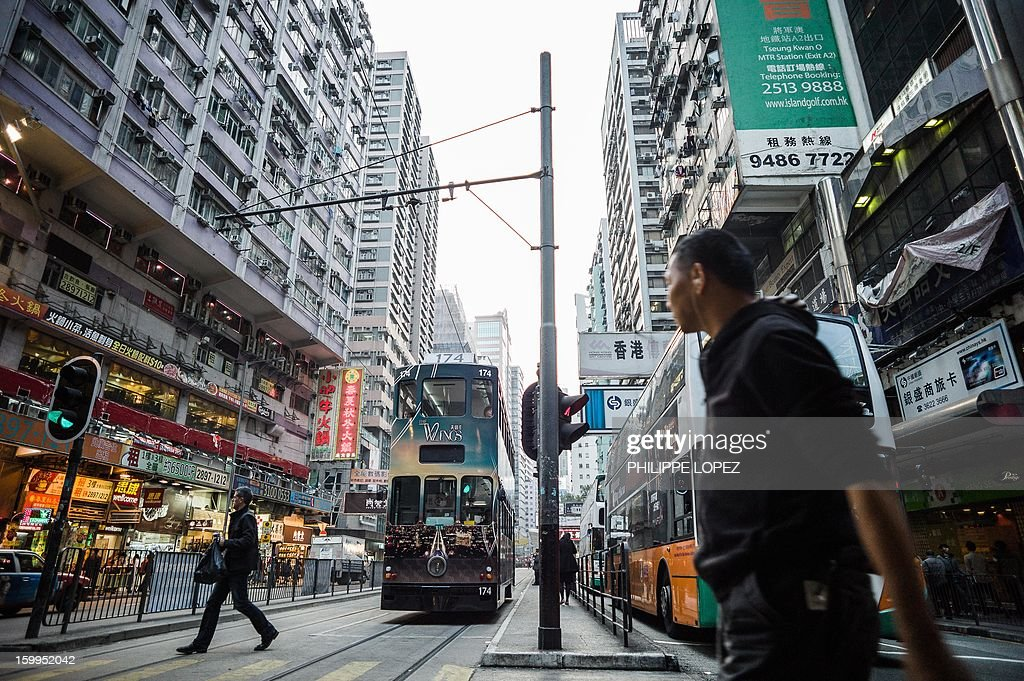 In this picture taken on January 17, 2013 a man crosses a street as a tram (centre L) approaches in Hong Kong. Trundling along slowly against a backdrop of glittering skyscrapers, Hong Kong's trams are entering a new phase of their life but their well-loved retro look is here to stay. AFP PHOTO / Philippe Lopez