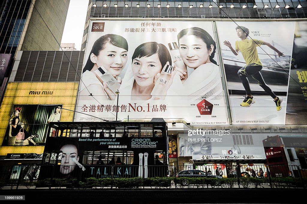 In this picture taken on January 17, 2013 a tram (bottom) drives past billboards in Hong Kong. Trundling along slowly against a backdrop of glittering skyscrapers, Hong Kong's trams are entering a new phase of their life but their well-loved retro look is here to stay. AFP PHOTO / Philippe Lopez