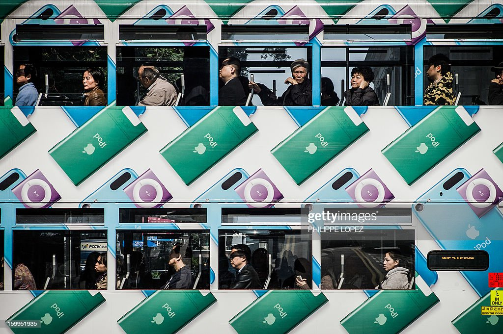 In this picture taken on January 17, 2013 commuters travel in a tram in Hong Kong. Trundling along slowly against a backdrop of glittering skyscrapers, Hong Kong's trams are entering a new phase of their life but their well-loved retro look is here to stay. AFP PHOTO / Philippe Lopez