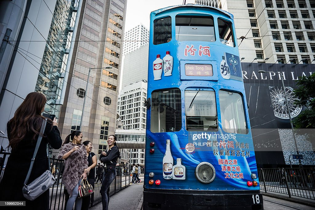 In this picture taken on January 17, 2013 women pose by a tram for a picture in Hong Kong. Trundling along slowly against a backdrop of glittering skyscrapers, Hong Kong's trams are entering a new phase of their life but their well-loved retro look is here to stay. AFP PHOTO / Philippe Lopez