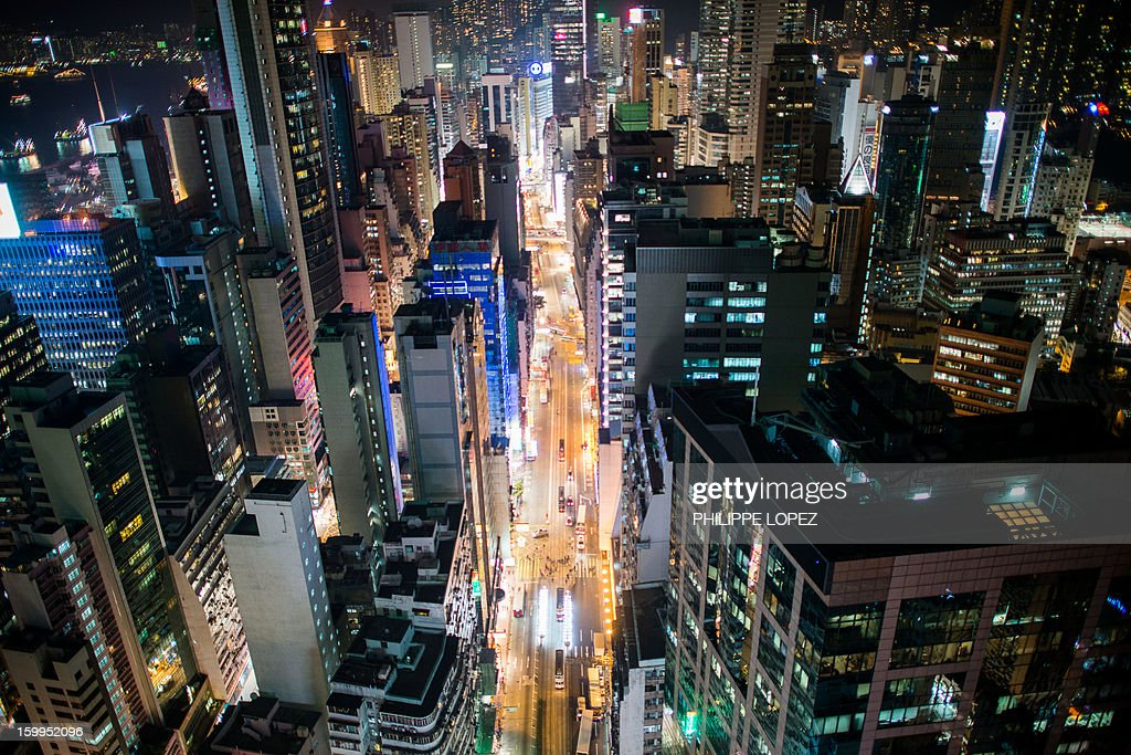 In this picture taken on January 21, 2013 trams are seen on their tracks in a street (C) surrounded by high rise buildings in Hong Kong. Trundling along slowly against a backdrop of glittering skyscrapers, Hong Kong's trams are entering a new phase of their life but their well-loved retro look is here to stay. AFP PHOTO / Philippe Lopez