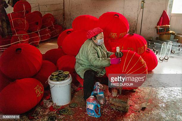 In this picture taken on January 22 a worker makes red lanterns at a factory in the village of Tuntou in Hebei province southwest of Beijing for the...