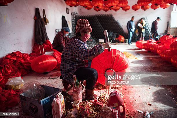 In this picture taken on January 22 workers make red lanterns at a factory in the village of Tuntou in Hebei province southwest of Beijing for the up...