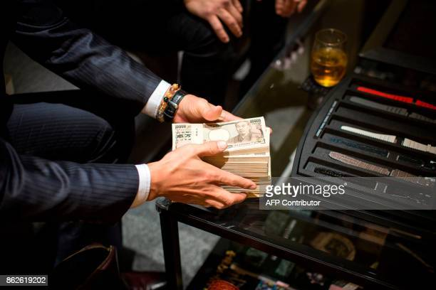 In this picture taken on January 27 a man puts stacks of Japanese yen notes on the table as he pays cash for buying a luxury watch at a store in...