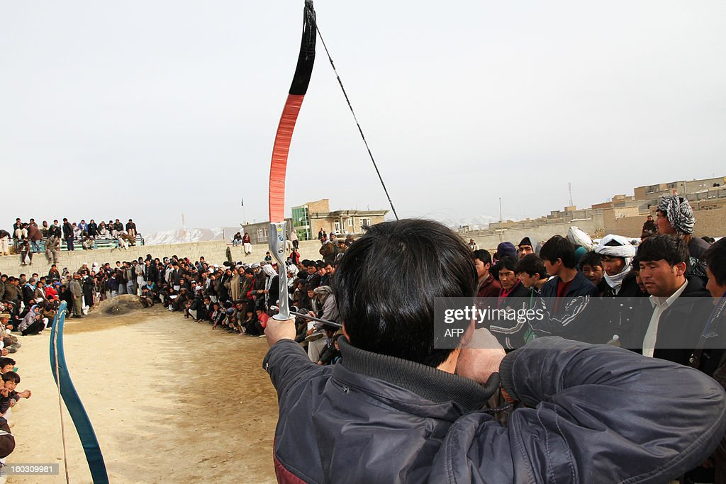 In this picture taken on January 28, 2013 Afghans gather to watch as a man participates in a traditional archery match in Ghazni city. Ghazni is one of the thirty-four provinces and one of Afghanistan's major cities with an estimated population of 141 000 people. It is located in the east of the country along the Kabul to Kandahar road. AFP PHOTO/ Rahmatullah Alizad
