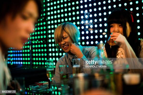 In this picture taken on January 28 a male host shares a lighter moment with a female customer at a host club in the Kabukicho redlight district in...